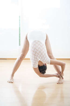 Beautiful girl doing  ballet and yoga in a white scenary