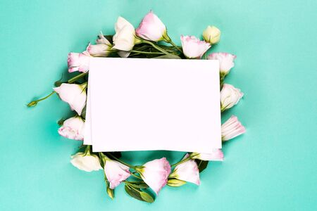 Photo pour Flowers composition. Wreath made of pink flowers eustoma with paper on blue background. Flat lay, copy space - image libre de droit