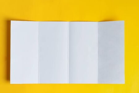 Photo pour Four-fold brochure mockup blank for writing letter or message above yellow background , copy space. Top view. - image libre de droit