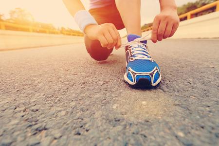 Photo pour young woman runner tying shoelaces on sunrise birdge road - image libre de droit