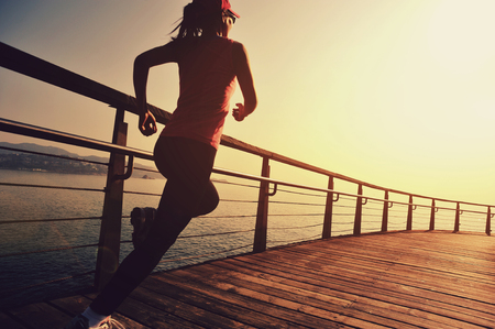 young fitness sports woman running on wooden boardwalk sunrise seaside