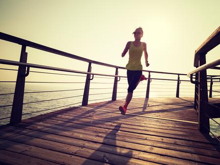 Photo pour sporty fitness female runner running on seaside boardwalk during sunrise - image libre de droit