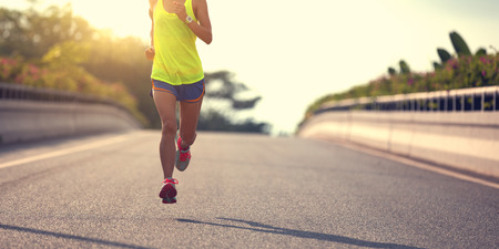 Foto de young fitness asian woman runner running on city road - Imagen libre de derechos