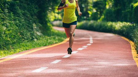 Foto de Healthy lifestyle woman runner running on morning park road - Imagen libre de derechos