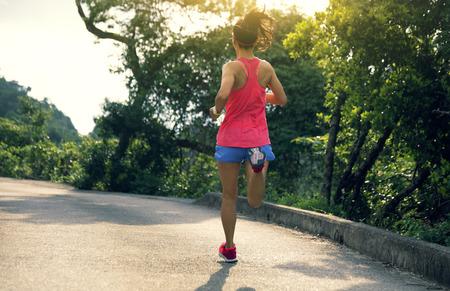 Foto de Sporty young woman in sportswear trail running on forest mountain path. Fitness girl jogging in Hong Kong - Imagen libre de derechos