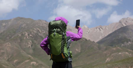 Photo for Successful woman hiker taking photo with smartphone on high altitude mountain top - Royalty Free Image