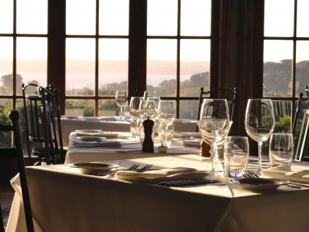 Gourmet restaurant tables await their guests in the afternoon light.