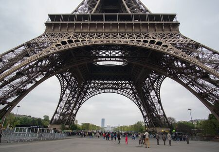 Photo pour Tourist waiting to go up at the base of Eiffel tower in the morning on April, 11 2017 in Paris, France - image libre de droit