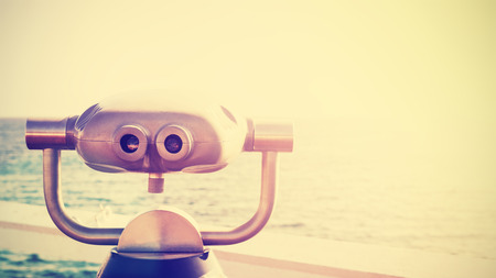 Vintage toned photo of a binocular pointed at horizon, future concept, copy space.
