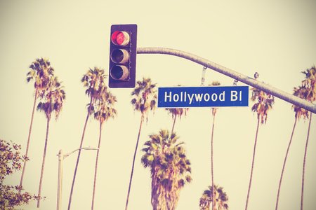 Vintage retro toned  boulevard sign and traffic lights with palm trees in the background, Los Angeles, USA.