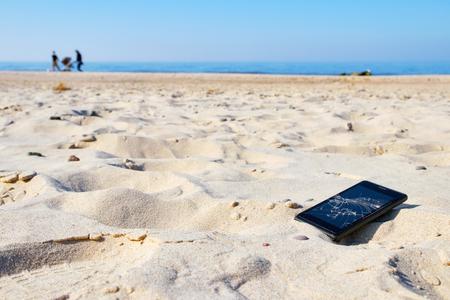 Photo pour Mobile phone with broken screen in sand on a beach, selective focus. - image libre de droit