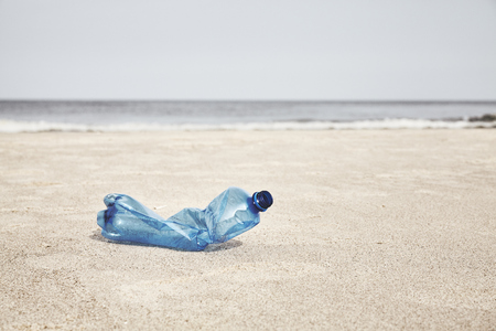 Foto de Empty plastic bottle on a beach, selective focus, color toning applied. - Imagen libre de derechos