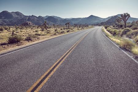 Photo pour Vintage stylized picture of a desert road at sunset, front focus on asphalt, California, USA. - image libre de droit