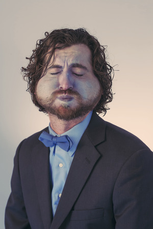 Bearded man holds his breath in anticipation and is turning blue