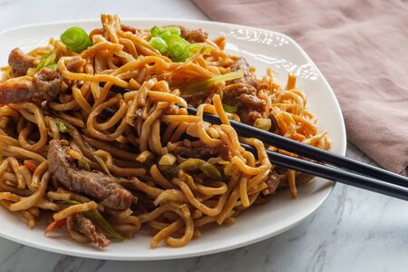 Photo for Eating Chinese beef lo mein noodles with chopsticks - Royalty Free Image