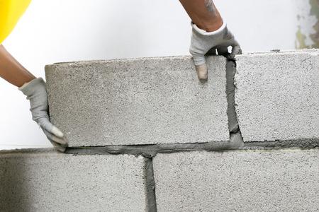 Foto de Close up of industrial bricklayer installing bricks on construction site, building walls. - Imagen libre de derechos