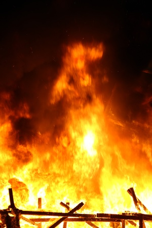 A picture of smoking ruins with big flames during the night