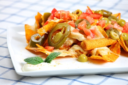 A picture of chicken nachos served on a white plate with sour cream