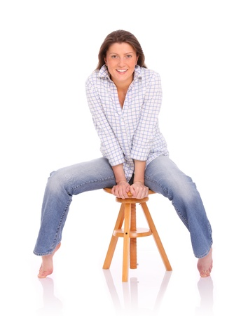 A picture of a young positive woman sitting and smiling over white background