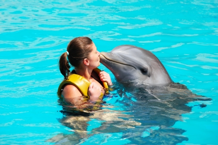 Photo for A picture of a young woman kissing a dolphin in a turquise water - Royalty Free Image