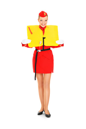 A picture of an attractive stewardess presenting a life vest over white background