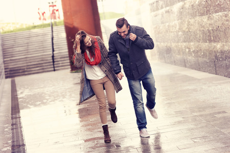 A picture of a young couple running in the rain in the cityの写真素材