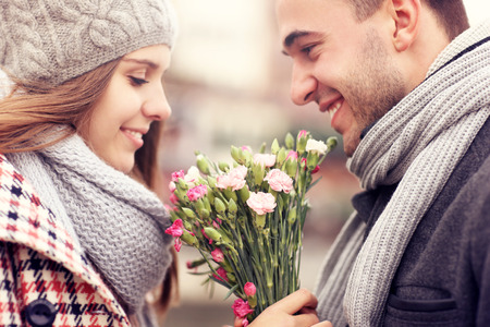A picture of a man giving flowers to his lover on a winter day