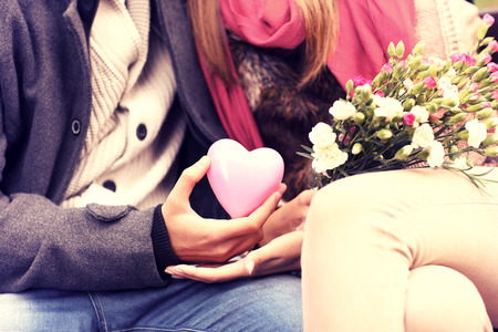 Photo pour A midsection of a romantic couple sitting on a bench in the park holding Valentines gift and flowers - image libre de droit