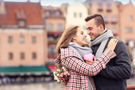 A picture of a couple on Valentine's Day in the city with flowers and heart
