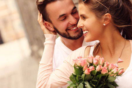 Foto de A picture of a young romantic couple with flowers in the city - Imagen libre de derechos