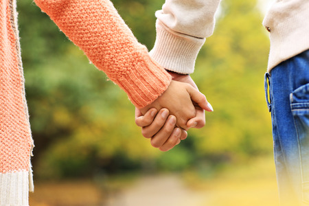 A picture of a couple holding hands in the park