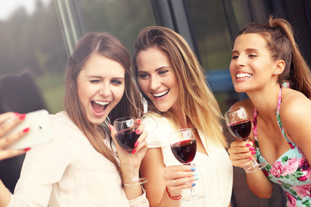 Picture presenting happy group of friends with red wine taking selfie