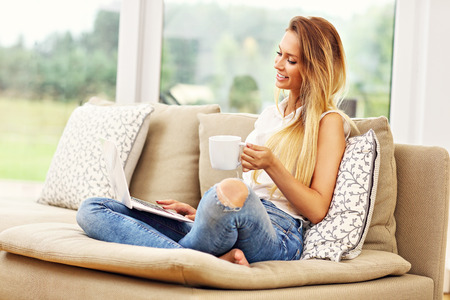 Photo pour Picture of young woman on couch with laptop - image libre de droit
