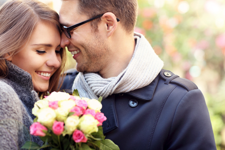 Photo for Picture showing happy couple hugging with flowers in the city - Royalty Free Image