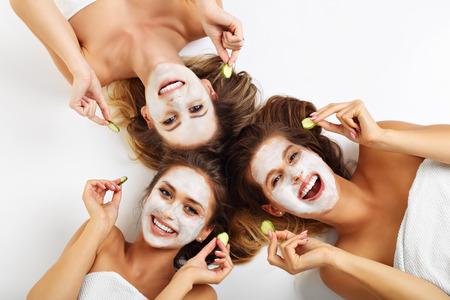 Foto de Picture showing three friends with facial masks over white background - Imagen libre de derechos