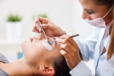 Photo pour Adult woman having eyelash extension in professional beauty salon - image libre de droit