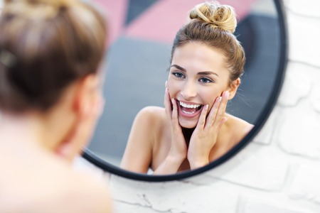 Photo pour Young woman cleaning face in bathroom mirror - image libre de droit