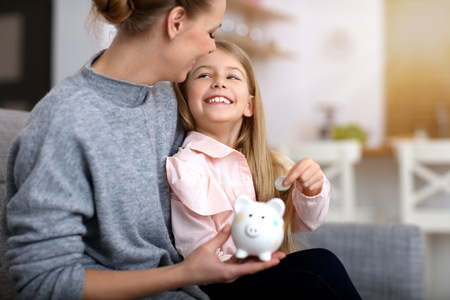 Photo pour Young girl and her mother with piggybank sitting at table - image libre de droit