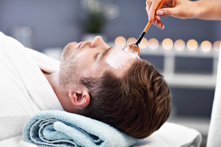 Photo pour Handsome man having facial in spa salon - image libre de droit
