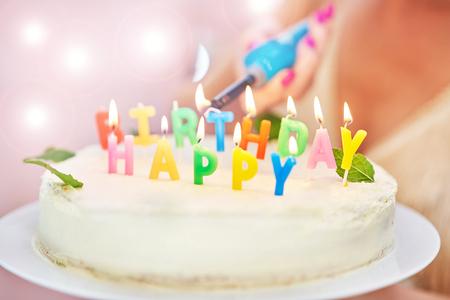 Photo pour Woman lightning candles on birthday cake - image libre de droit