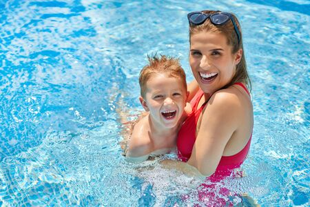 Photo for Cute boy with his mother playing in swimming pool during summer - Royalty Free Image