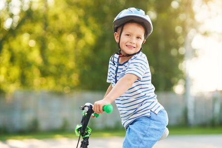 Foto de Happy 3 year old boy having fun riding a bike - Imagen libre de derechos