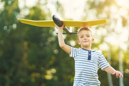 Photo pour Happy 3 year old boy having fun playing with big plane outdoors - image libre de droit