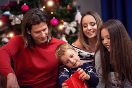 Photo pour Beautiful family with presents over Christmas tree - image libre de droit