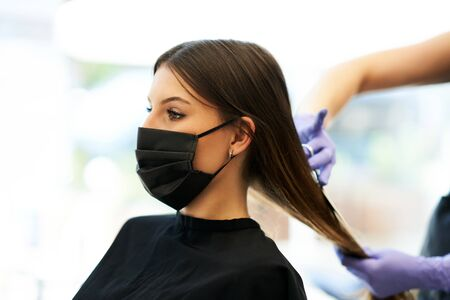 Photo pour Adult woman at hairdresser wearing protective mask due to coronavirus pandemic - image libre de droit