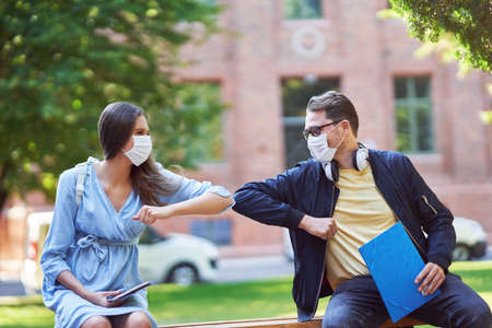 Photo for Couple of students in the campus wearing masks due to coronavirus pandemic - Royalty Free Image