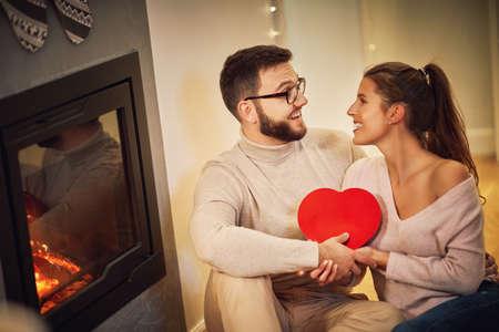 Foto de Adult couple with present over fireplace - Imagen libre de derechos