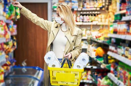 Foto für Adult woman in medical mask shopping for groceries - Lizenzfreies Bild