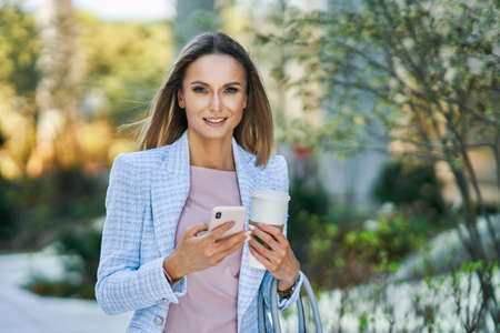 Photo for Adult attractive Business woman with smartphone and coffee walking in the city - Royalty Free Image