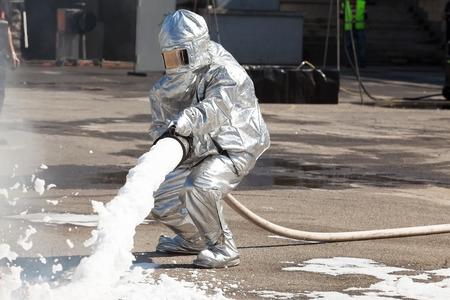 Firemen spray firefighting foam